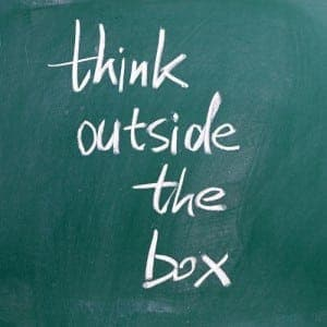 The phrase Think Outside the Box written in white chalk on a bla